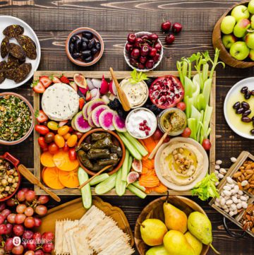A grazing board with a lot of vegan appetizers in a large wooden tray and small plates with fruits, salads, and nuts. Recipe at Spoonabilities.com