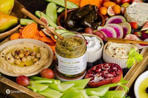 A jar of roasted eggplant dip in the center of the vegan appetizer board. The tray has dips, vegetables, fruits and vegan cheese. Recipe at Spoonabilities.com