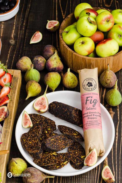 Round white plate with slices of vegan fig salami and next a whole vegan salami with the label in the original packaging. Behind the plate fresh figs. Product available at Spoonabilities.com