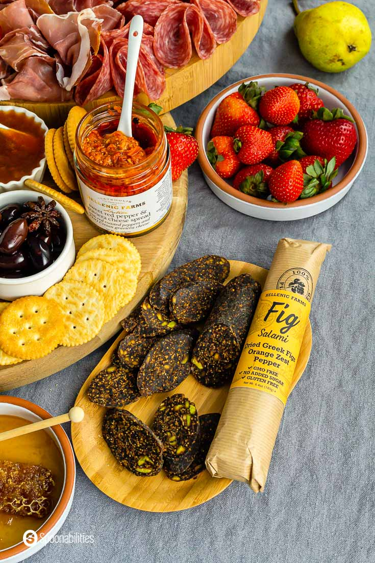Vegan Fig Salami with Orange Zest and Pepper in the package in a wooden tray with some slices of the vegan salami. Check this vegan product at our shop at Spoonabilities.com