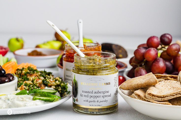 A open jar of roasted Aubergine and red pepper spread from Hellenic Farms. The jar has a white spoon inside. Around the jar are plates with some mezze dishes. Product available at Spoonabilities.com
