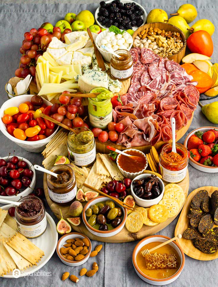 Amazing Grazing board with cured-meats, cheeses, gourmet products, olives, and more. Check Charcuterie Board Ideas recipe at Spoonabilities.com