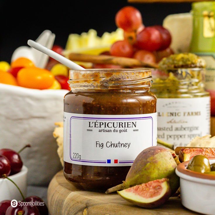 A close-up of the fig chutney from L'Epicurien and in front of the jar a whole fresh fig and a piece in a quarter. Product available at Spoonabilities.com