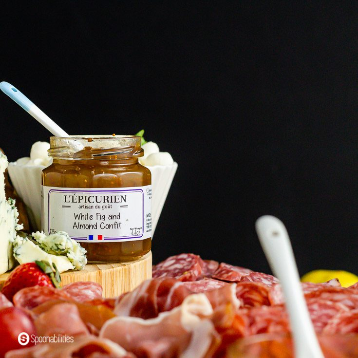 A jar of white fig and almonds confit next to the blue cheese and surrounded by the cured meats. Recipe at spoonabilities.com