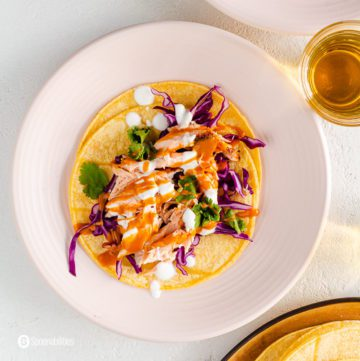 A round pink plate with an open face salmon tacos with red cabbage, Mexican crema, spicy chipotle sauce, and cilantro leaves. Recipe at Spoonabilities.com