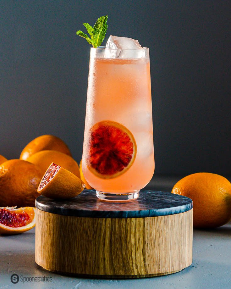 A beautiful tall cocktail glass in a wooden pedestal and in the background fresh blood oranges. Recipe at Spoonabilities.com