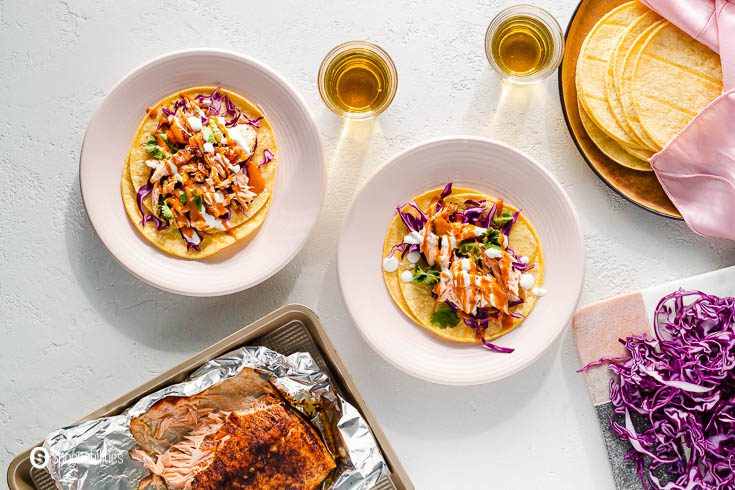 Overhead photo with two pink plates with air fryer salmon tacos. On the top right side is a plate with corn tortillas, next to that plate shredded red cabbage, and on the left bottom side a tray with the salmon cooked in the air fryer. Recipe at Spoonabilities.com