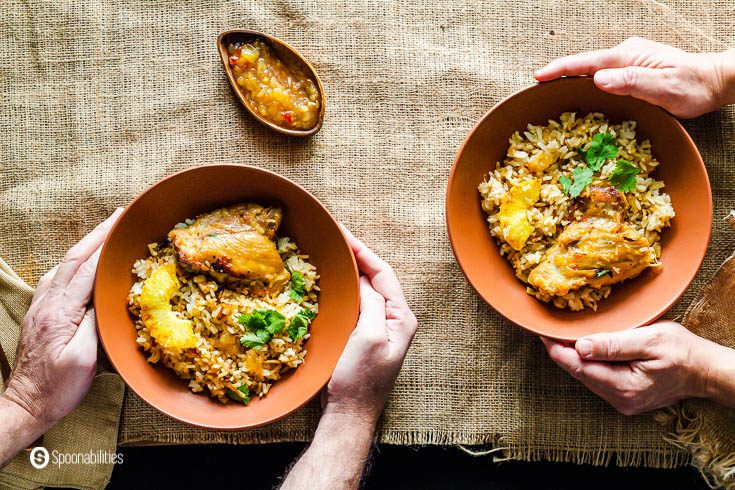 Two people hands holding two terracotta color bowls with chicken and rice casserole. Recipe at Spoonabilities.com