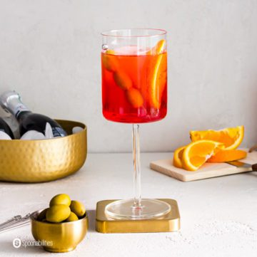 A glass wine in the center of the photo with the Italian cocktail Aperol Spritz Veneziano with Green Olive. The glass is on top of a golden metal coaster and near the glass a small bowl with green Greek Olives. Recipe at Spoonabilities.com