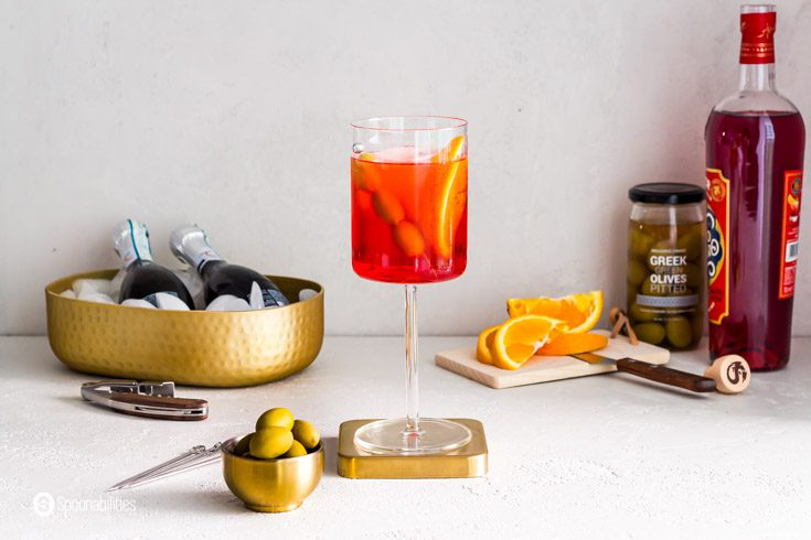 The Italian summer cocktail served in a glass wine. In the background a bottle of prosecco, Green Greek olives, and the aperitif Aperol. Recipe at Spoonabilities.com