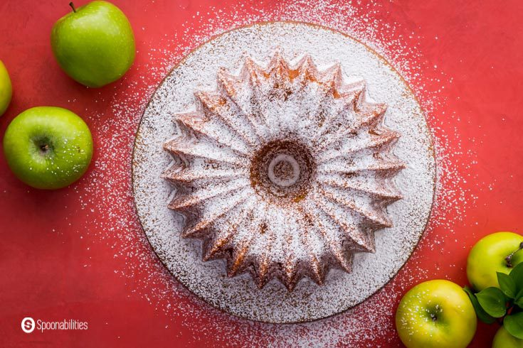 Overhead photo with an olive oil cake on a round plate, The cake has powdered sugar and some Granny Smith apples around the picture frame. Recipe at Spoonabilities.com
