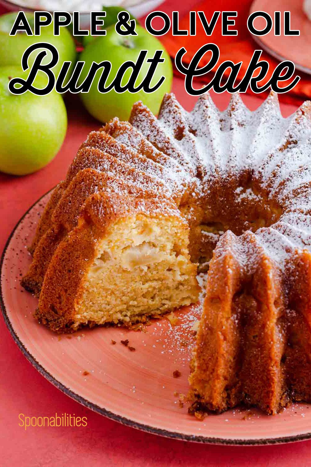 The apple and olive oil bundt cake is on a large plate, one piece of the cake is out, and it's showing the inside of the cake. The cake is dusted in powdered sugar. Recipe at Spoonabilities.com