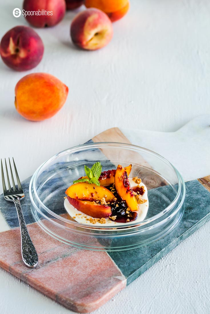A glass plate on top of a marble board with a peach dessert on the plate with baked peaches, black cherry preserves, and Creme Fraiche. Recipe at spoonabilities.com