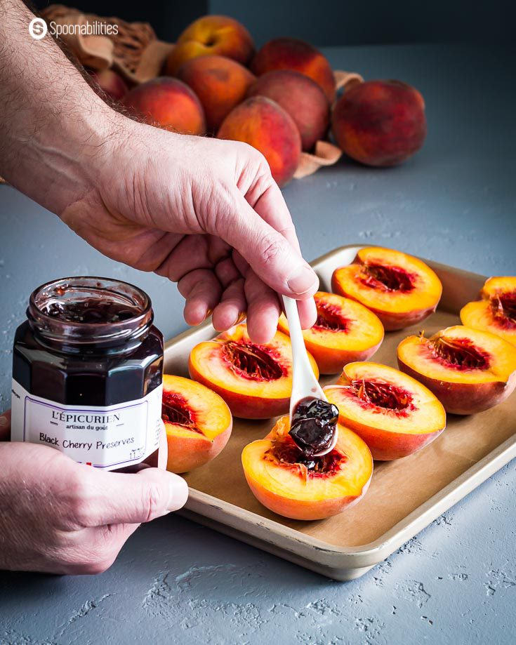 A baking tray with peaches cut in halves and a hand with a jar of black cherry preserves, and the other hand with a spoon putting the jam on the peach. Recipe at spoonabilities.com