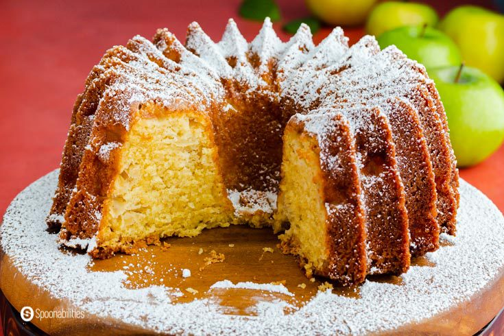 A bundt cake with a piece out, and it's showing the inside crumb of the cake. The cake is made out of olive oil and apples. Recipe at Spoonabilities.com