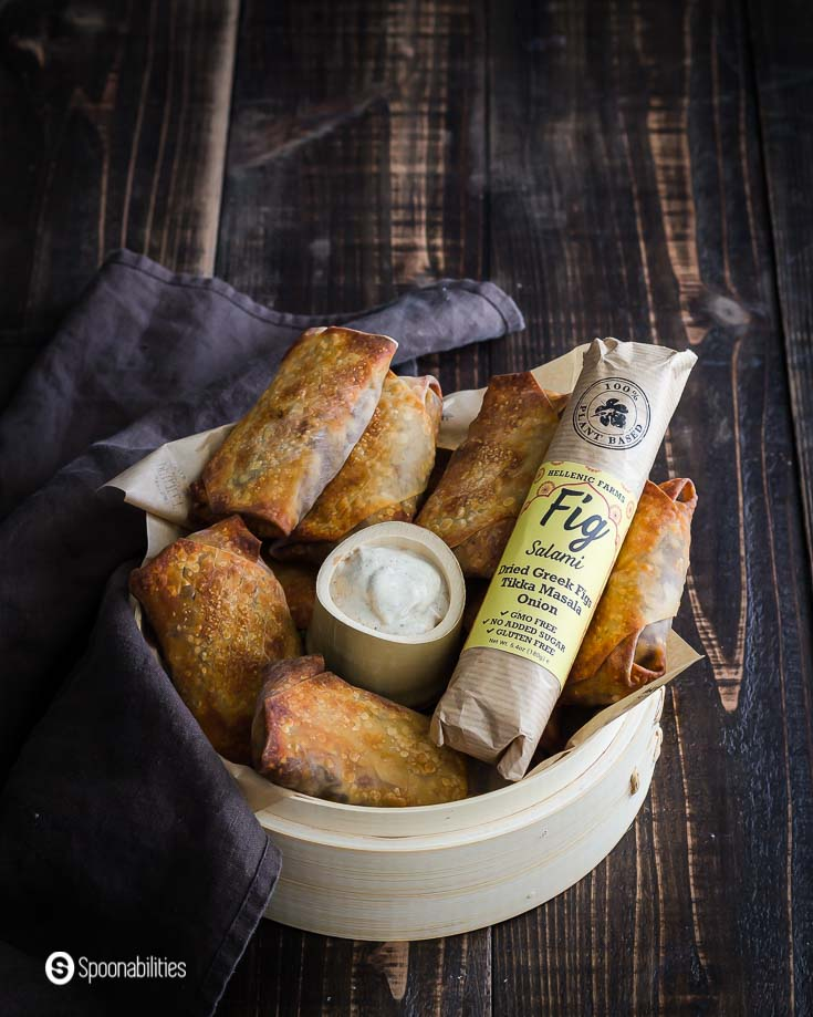 A basket with some air fryer egg rolls which are vegan made with vegan fig salami. Baked in the air fryer. Recipe at Spoonabilities.com