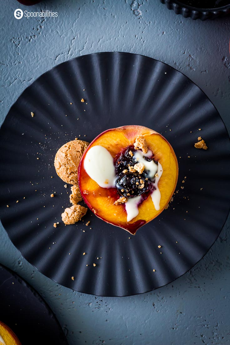 Beautiful black plate with a grilled peach halve with cherry jam, crème fraiche, and amoretti cookies. Recipe at Spoonabilities.com