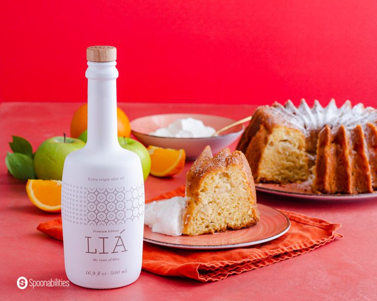 A beautiful Lia Extra Virgin Olive oil bottle is placed in front of a piece of olive oil cake. In the background, the bundt cake and whipped cream in a small bowl. Recipe at Spoonabilities.com