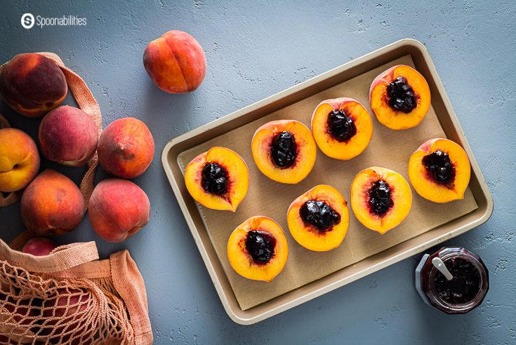 Baking tray with eight peach halves with black cherry jam in the center, in the frame, you will see a bag on the left side with fresh peaches and on the right side an open jar of jam. recipe at spoonabilities.com
