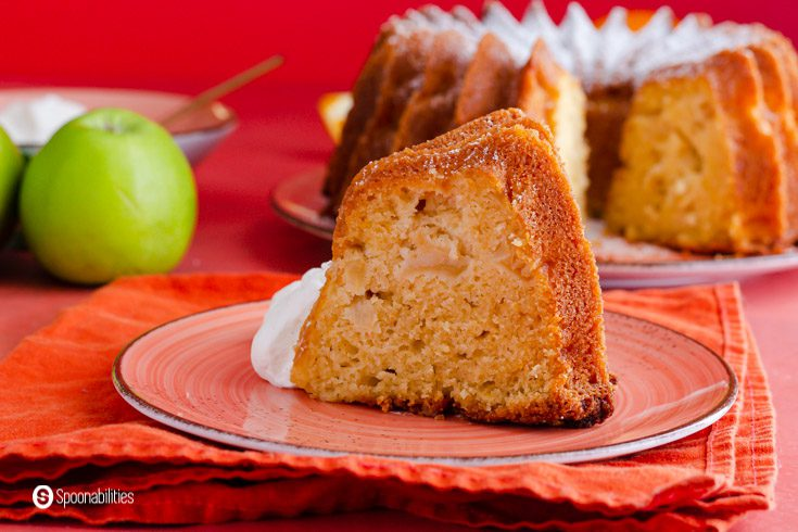 A piece of apple cake made out of olive oil and Granny Smith apples. The slice of cake is on a small plate on top of an orange napkin. Recipe at Spoonabilities.com