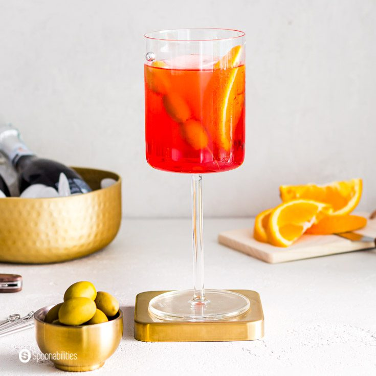 A close up of the famous Italian cocktail Aperol Spritz served in a glass wine. The glass is on top of a golden metal coaster. In a small bowl some green Greek olives. recipe at Spoonabilities.com