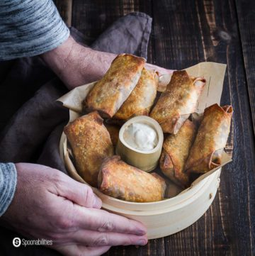 Two hands holding a steam basket with some vegan egg rolls cooked in the air fryer. In the center is a little container with garam masala yogurt sauce. Recipe at Spoonabilities.com