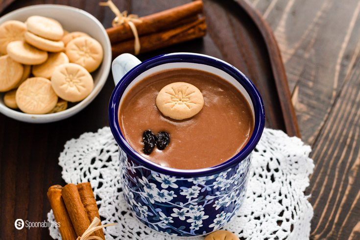 A close-up of a blue printed cup with Habichuelas con dulce garnished with milk cookies and raisins. Learn the ingredients at Spoonabilities.com