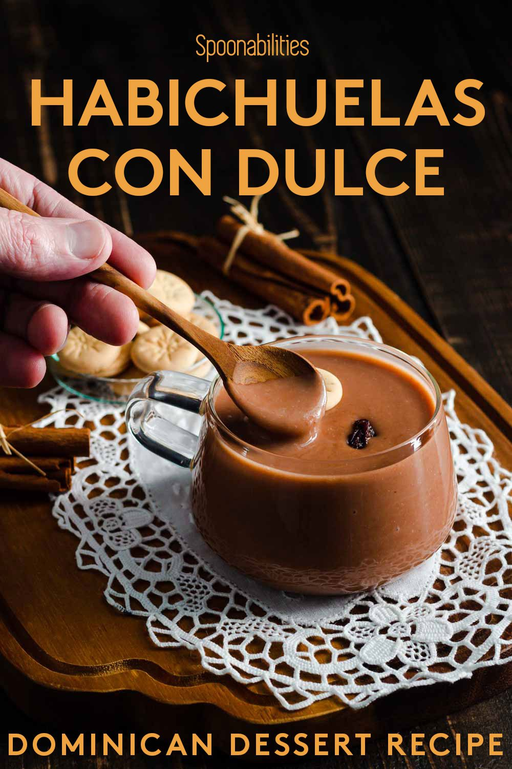 A glass cup on top of a wooden serving board with Habichuelas con dulce. This Dominican Dessert is made out of red kidney beans, coconut milk, evaporated milk, sugar and other spices. Recipe at Spoonabilities.com