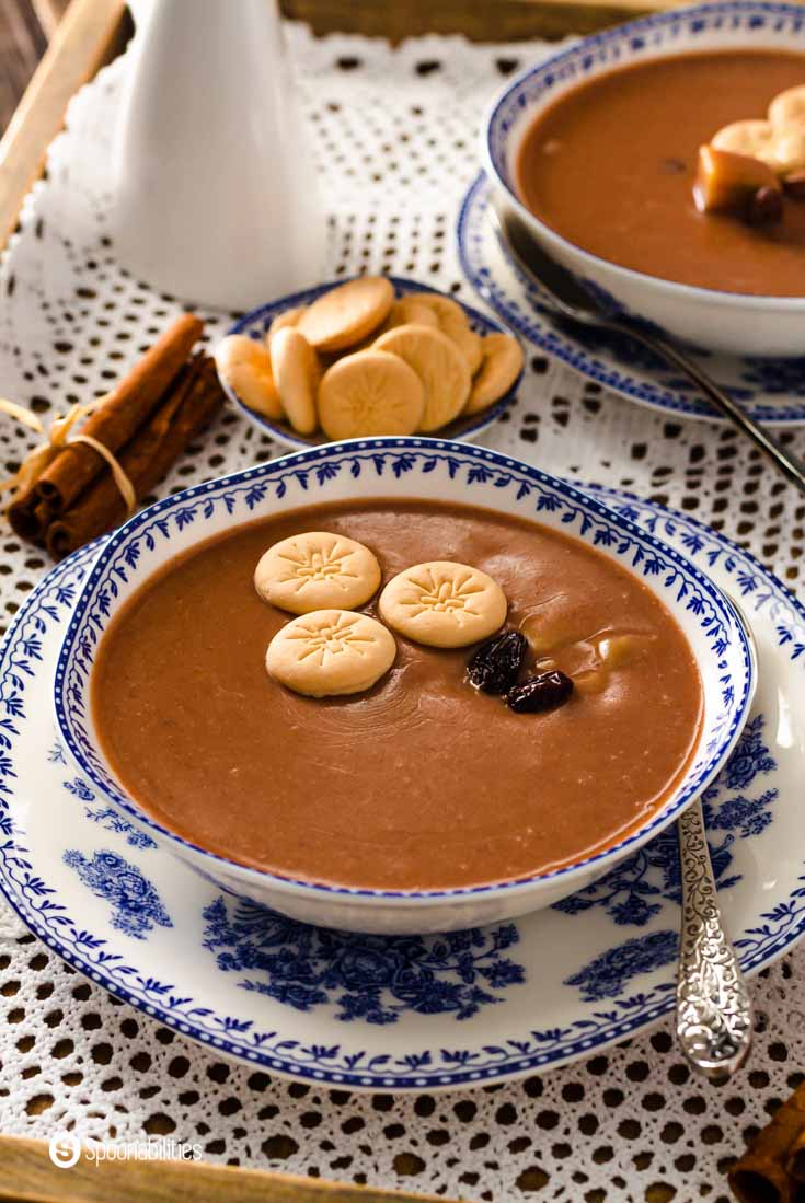 An antique-looking bowl with blue imprints with a traditional Dominican dessert in the bowl. This dessert is made with red kidney beans, coconut milk, evaporated milk, cinnamon sticks, whole cloves, sugar, and raisins. Learn more about this Easter dessert at @spoonabilities.com