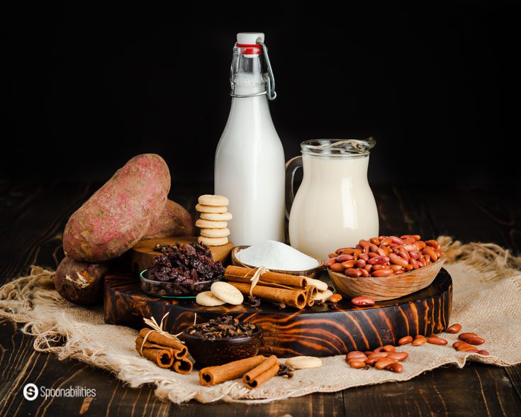 The photo shows all the ingredients used in this Dominican Easter recipe, and some of the ingredients are red kidney beans, coconut milk, evaporated milk, sugar, cinnamon sticks, white sweet potatoes, milk cookies, and raisins. Learn more about this Dominican recipe at @Spoonabilities.com