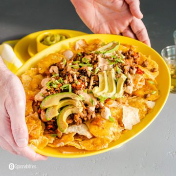 Two hands holding a yellow oval serving plate with loaded vegan nachos. Recipe at Spoonabilities.com