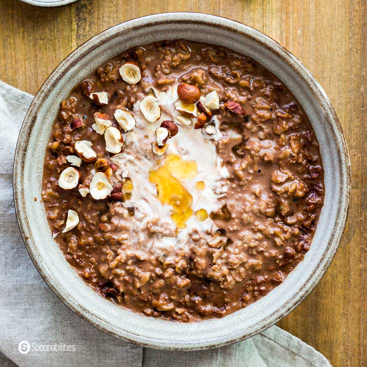 tight close-up of chocolate oatmeal with hazelnut and honey topping