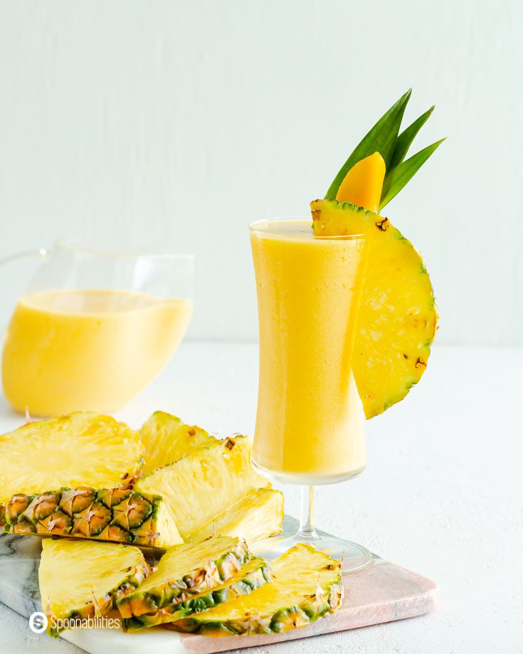 slices of pineapple next to a tall glass of mango pina colada