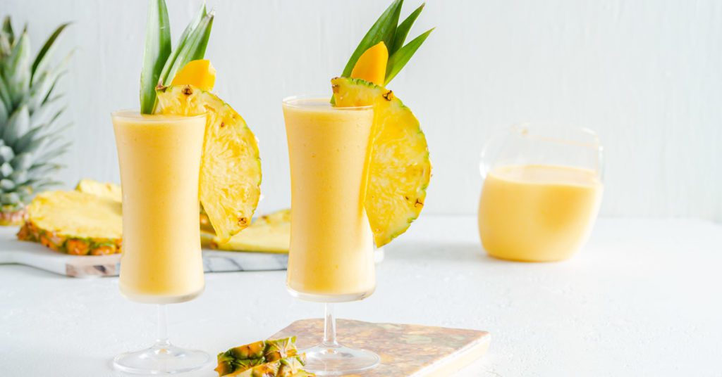 Two tall concave glasses filled with mango pina colada garnished with pineapple leaves and slices