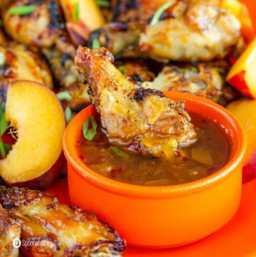 close up of chicken wing dipped in hot pepper peach bourbon sauce
