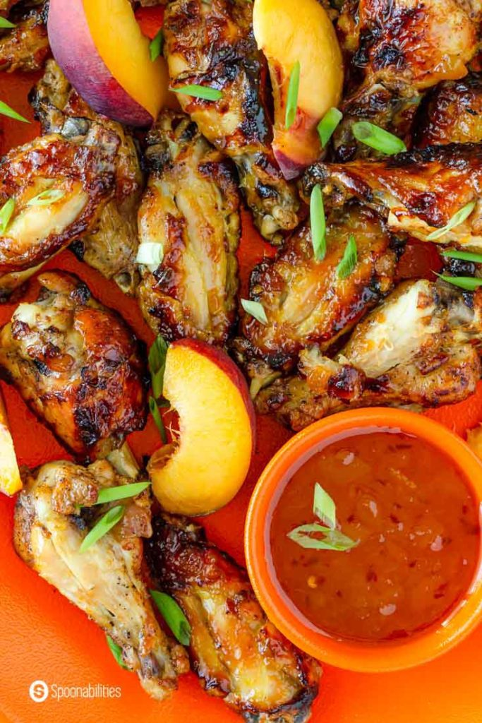 close up overhead photo of chicken wings, pepper peach sauce and sliced peaches
