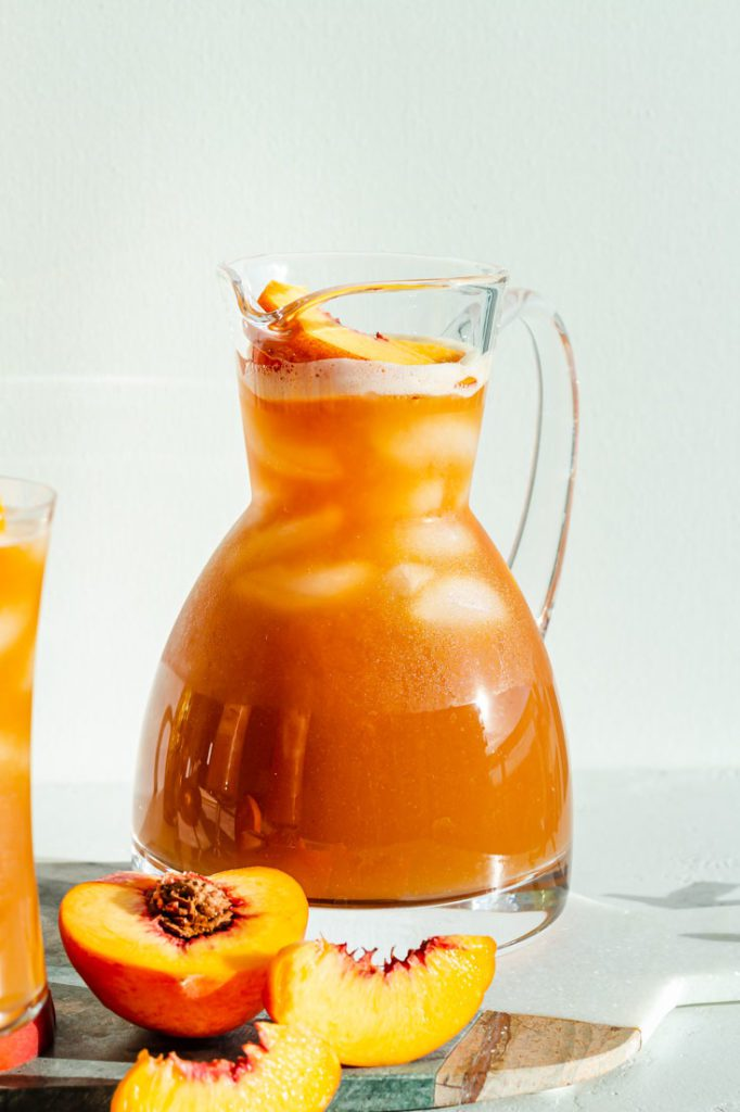 close up of large pitcher of peach iced tea