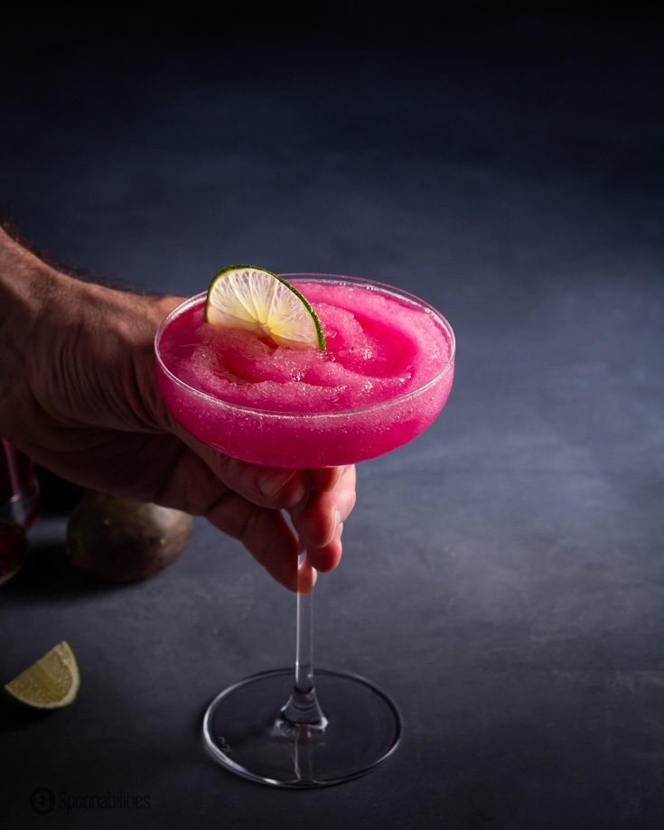 A hand holding a coupe glass with a frozen margarita flavored with prickly pear syrup. Recipe at Spoonabilities.com