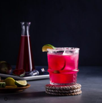 A rock glass on a wicker coaster with a prickly pear margarita. Recipe at Spoonabilities.com
