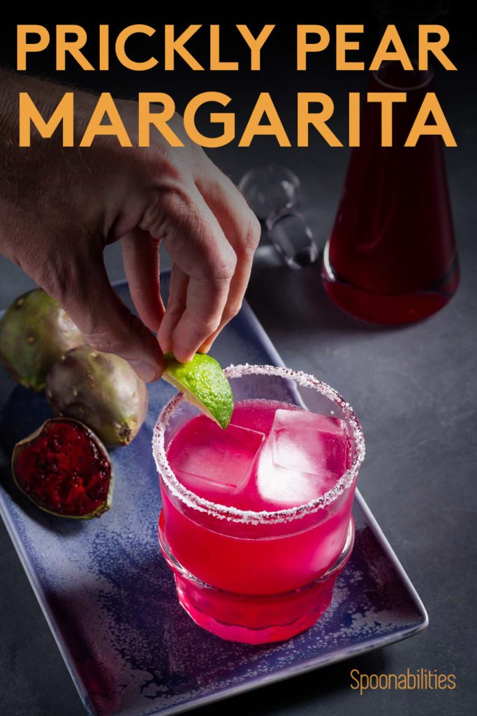 A rock glass with prickly pear margarita and a hand putting a lime on the glass. Recipe at Spoonabilities.com