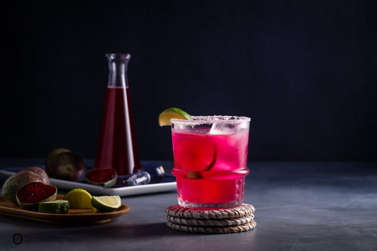 A rock glass on a wicker coaster with a prickly pear margarita. In the background a bottle with the prickly pear syrup and prickly pear cactus fruit. Recipe at Spoonabilities.com