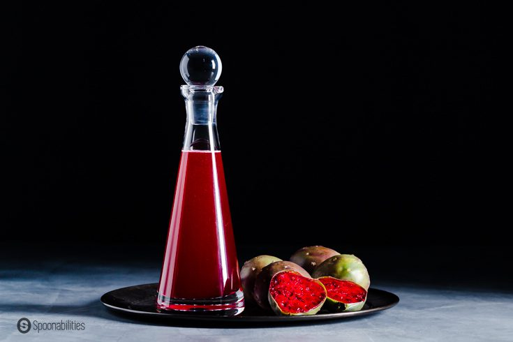 A glass bottle on top of a metal tray. The bottle has flavored simple syrup with prickly pear. Recipe at Spoonabilities.com