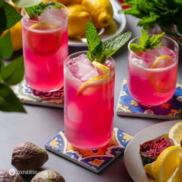 Three glasses on top of a coaster with Prickly Pear Juice Sparkling Lemonade and garnished with fresh mint and sliced lemon.