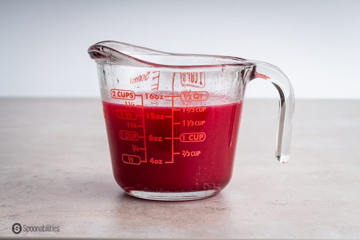 Prickly pear syrup in a measuring cup. Recipe at spoonabilities.com