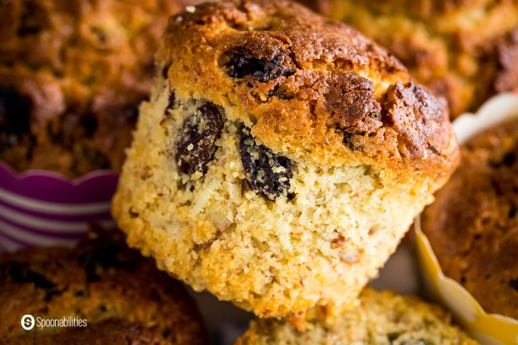 The photo has one almond sourdough muffins, it shows the inside with raisins and pieces of almond slices. Recipe at Spoonabilities.com