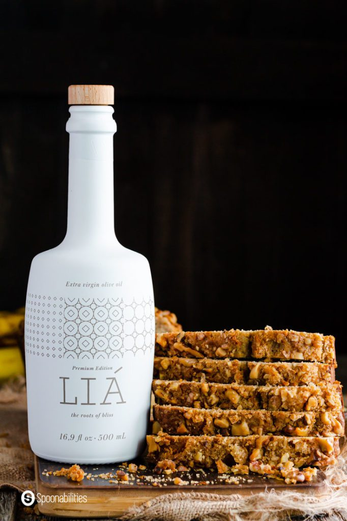 A Bottle of Lia Extra Virgin Olive oil next to a tower of slices of banana bread made with sourdough discard. Recipe at Spoonabilities.com